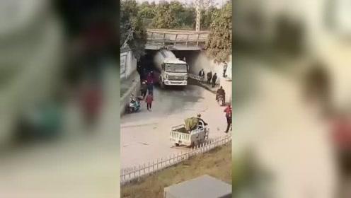 安徽固镇县一水泥罐车卡铁路地下道无法动弹 地下道受损严重