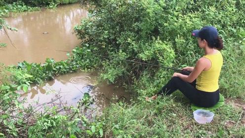 小妹用蜈蚣肉做鱼饵,静坐在水坑边悠然钓鱼,转眼马上有大收获了