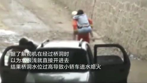 小车误入积水桥洞熄火一家三口被困 消防员趟水将其背出