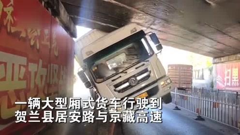 """宁夏一集装箱卡车""""钻桥洞""""被卡,车辆倾斜:卡得好有型"""