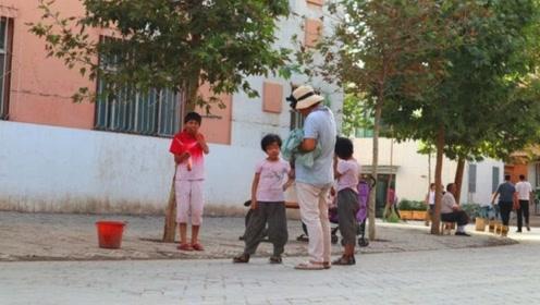 在新疆喀什古城,小孩向客索要一元,本地人却说不能给