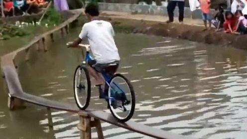 高手!小伙子淡定单手骑自行车过独木桥。看傻了一旁的观众!