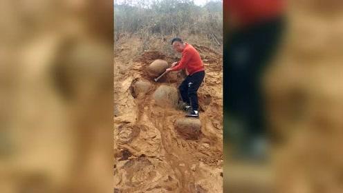 男子野外石壁上挖巨石,巨石脱落差点砸到同伴,好危险!