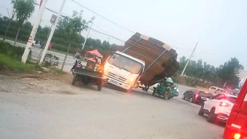 这就是严重超载的后果,差点把三轮车碾压了,这种司机太缺德了!