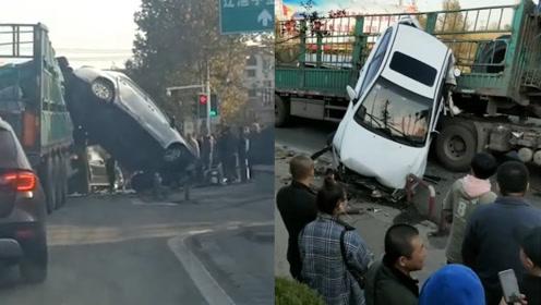 """辽宁一小轿车遭挤压车身""""倒立""""挂在大货车上 路人吐槽:飞车顶上去了"""