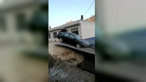 把车开到别人的铁皮房上,还好没漏下去!