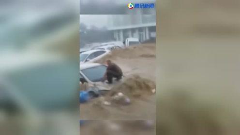 山洪奔腾而下 男子蹲在车上被冲走