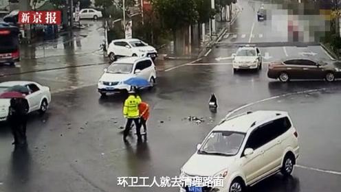 环卫工清扫车祸碎片 交警撑伞为其挡雨