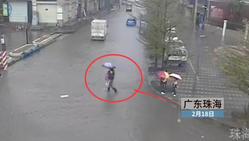 暖心!暴雨致路面积水 两路人轮流抱多个孩子通过