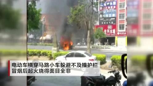 电动车横穿马路小车躲避不及撞护栏 冒烟后起火烧得面目全非