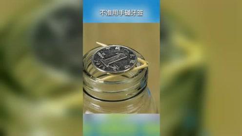 不用手碰,有什么办法让硬币自动掉下去?