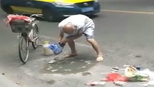 大爷看见路面有坑,骑自行车带水泥来修补,真是太有正能量了!