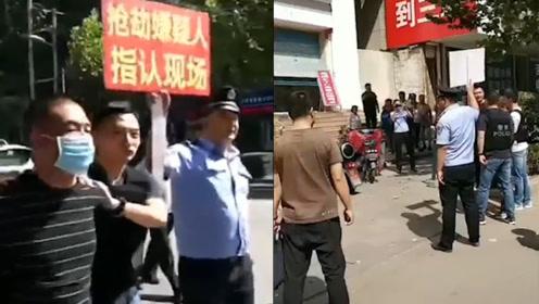 男子银行内持刀抢劫后被抓 警方押着嫌疑人指认现场大量市民围观