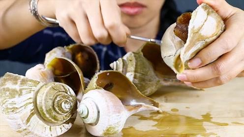 美女吃巨大田螺,沾上调料汁吃一口,闭眼慢慢的品尝味道