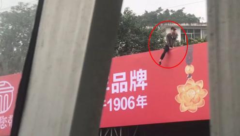 """年轻小伙""""骑""""坐高空广告牌疑似轻生 一条腿悬空情况危险"""