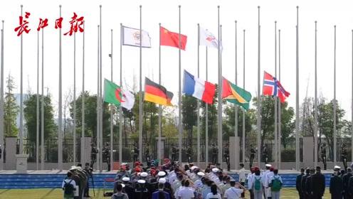 伴着军运会会歌,五面外国国旗率先在军运村升起