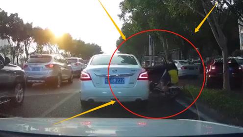 汽车停下后不看后方路况就打开车门下人,经过的电动车母子被撞倒在花坛里!