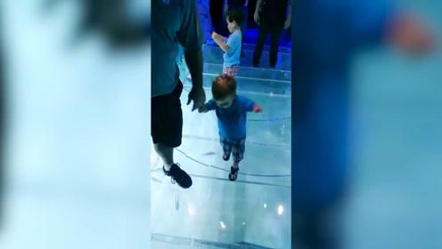 男孩在玻璃上行走,每一步都非常小心,真是太可爱了!