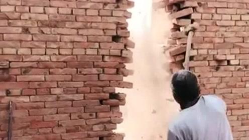 老大爷可真够厉害的,这么大的一面墙,硬是用锤子给砸开了!