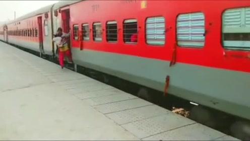 火车还在行驶,一位妇女抱着孩子就下车了,看了好几遍才看清楚