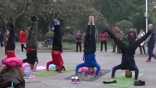硬核老人公园组团健身 独创倒立唱歌法走红