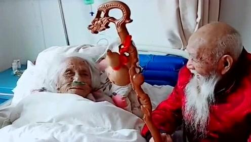 爷爷坐在妹妹床前,拿着自己的拐杖晃着小葫芦逗妹妹开心,真好!