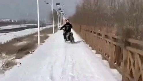 小伙骑着摩托车在雪地上行驶,路面非常滑,车子不能正常行驶!