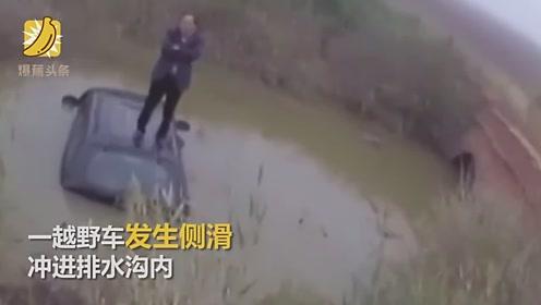操作不当越野车冲进排水沟驾驶员站车顶等救援