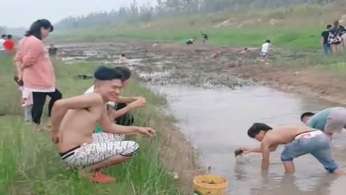 村里的大河断流了,村民们组队下河摸鱼,抓了满满一水桶!