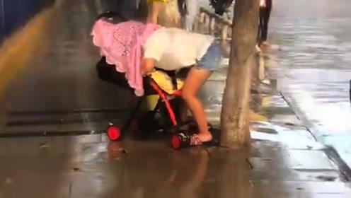 下这么大的雨,出门也没带伞,妈妈只能这样给孩子挡雨了