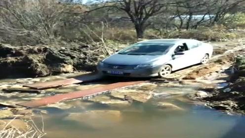 进村唯一的路被水淹了,司机找块板子就往上开,能不能成功看你了