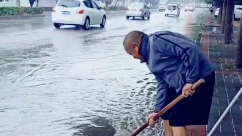 下雨后路上积水,大叔主动清理下水道,看着让人心暖!