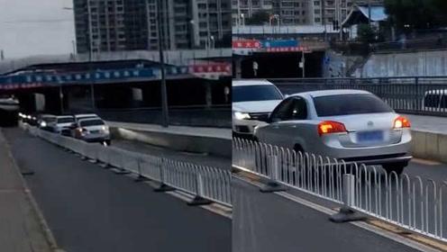 像极了犯错的你!逆行轿车被车流顶着步步倒退,交警通报处罚