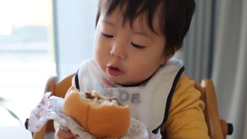 小宝宝第一次吃汉堡包,撅着小嘴一口一口的吃,还跟妈妈说真好吃