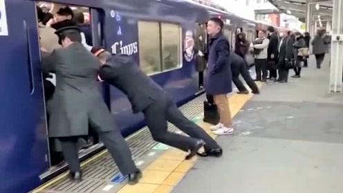日本的地铁,里面挤得满满的人,门都关不上了工作员使劲往里塞!
