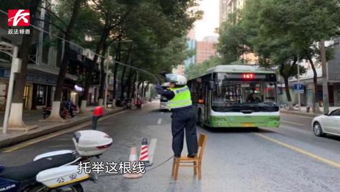 街道中央电线脱落,交警站凳子上单手托举,成最美风景线