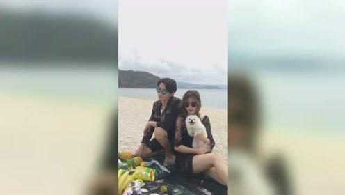 一家三口幸福的坐在沙滩上拍照,幸福感十足!图片