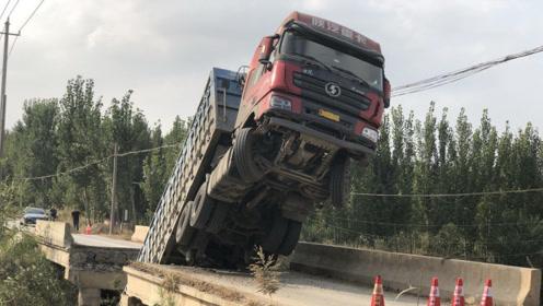 满载石料货车压塌桥梁,车头几乎直立,车厢插入河中