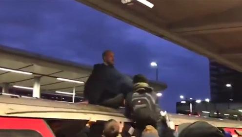 极端环保示威者爬上伦敦地铁车顶 被上班族一把薅下来痛打