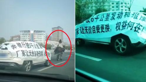 维权新创意?女子骑马拖奔驰车游街维权 引路人围观拍照
