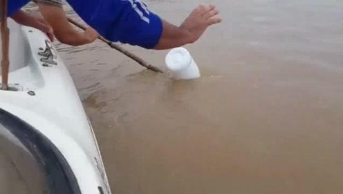 捡起河中的一个瓶子,没想到下面竟挂着一条大鱼