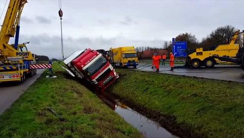 大卡车翻车掉沟里,司机急坏了,大吊车赶来救援
