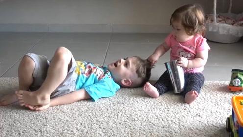 哥哥被妹妹拽头发,哥哥假装很疼哇哇大叫,却又故意逗妹妹拽