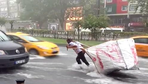 城里下雨道路积水了,没想到小伙还拖着车一路逆行,挣钱不易啊!