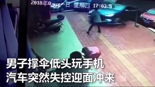 男子撑伞低头玩手机 汽车突然失控迎面冲来