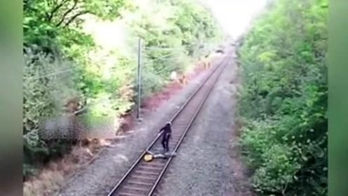 男子正推着车经过火车道,监控拍下这惊险一幕