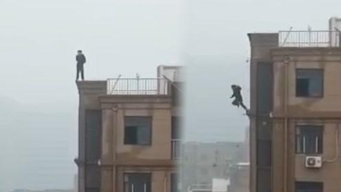男子轻生欲跳楼 犹豫之际楼顶边缘突然断裂