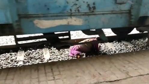 印度老妇人抄近路穿越铁轨 恰巧火车驶来 情急之下趴在铁轨上躲过一劫