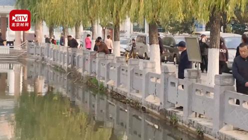 大妈们湖边买鱼放生 多名男子在放生现场捞鱼