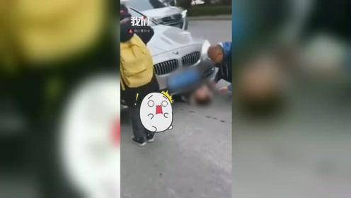 贵州凯里一女童被卷入车底 数十人抬车施救